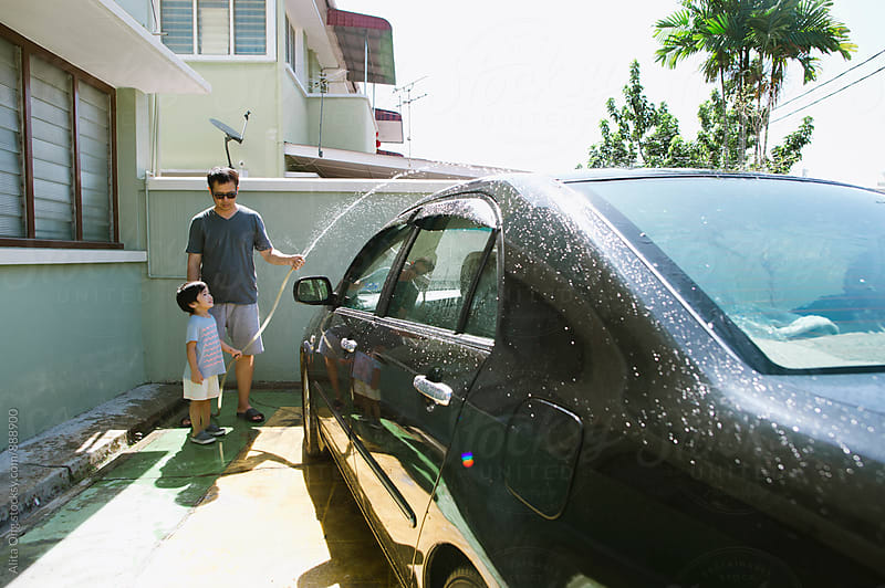 Dad and son washing car on sunny day by Alita Ong for Stocksy United