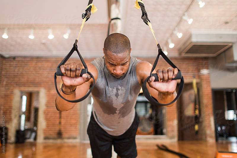 Muscular African-American man using exercise bands by Jakob for Stocksy United