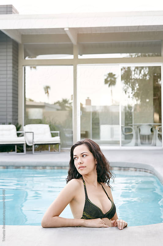 Hispanic woman relaxing in pool at modern design home by Trinette Reed for Stocksy United
