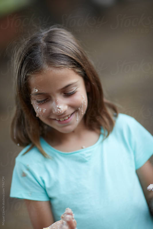 Pretty young girl smiling in a birthday party with some cake on her nose by Miquel Llonch for Stocksy United