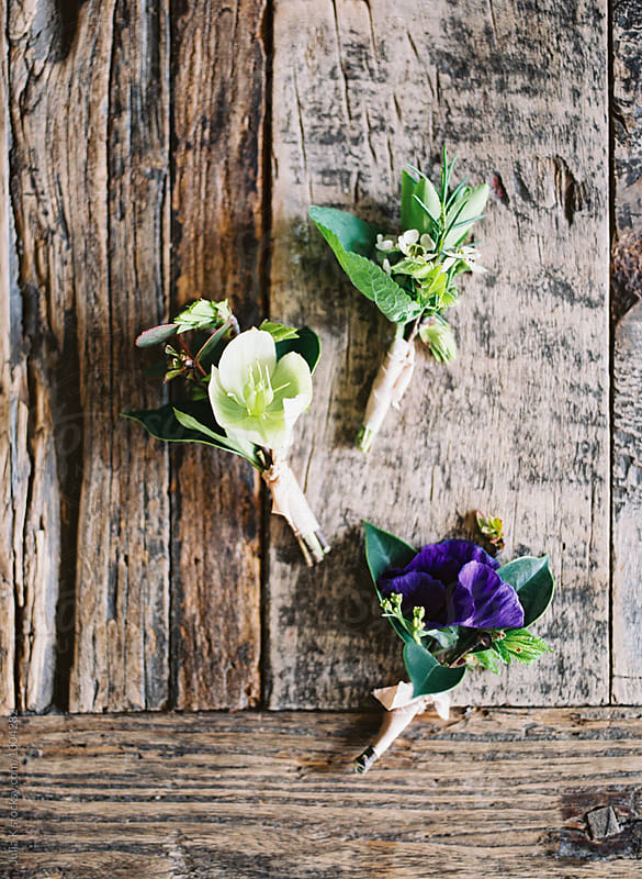 Tiny boutonnieres on a rustic background by Julia Kaptelova for Stocksy United