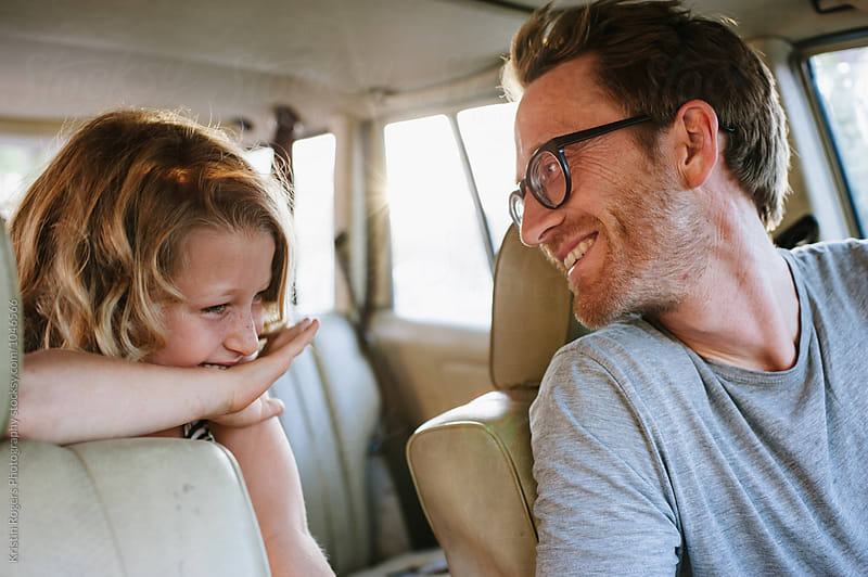 Dad and daughter laughing in car together by Kristin Rogers Photography for Stocksy United