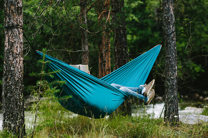 Young woman reading a book in hammock by Aleksandar Novoselski for Stocksy United