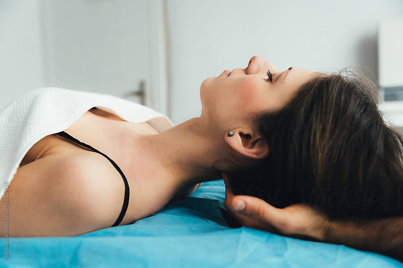 Relaxed young woman lying on her back on a bed receiving a massage on the back of her head by Inuk Studio for Stocksy United