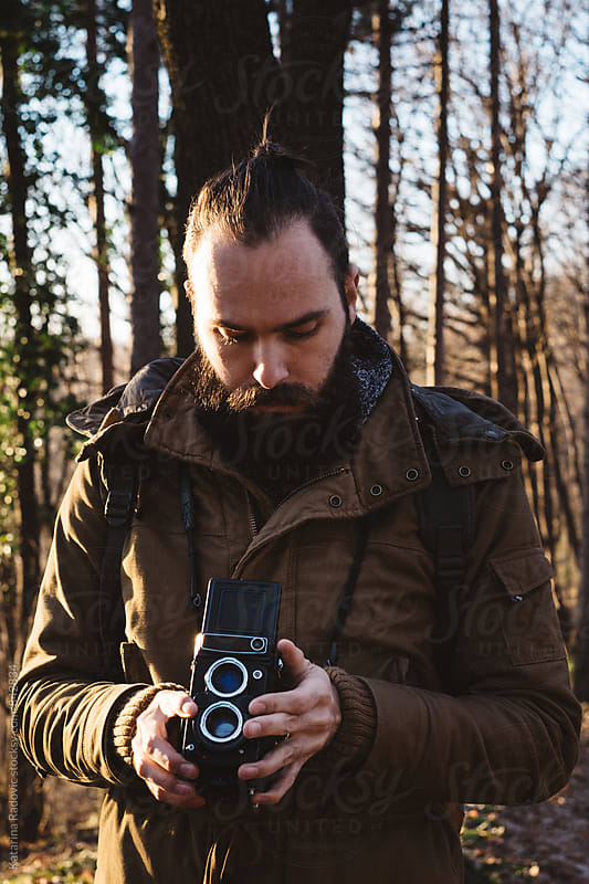Handsome Bearded Man Standing in the Woods With His Vintage Camera by Katarina Radovic for Stocksy United