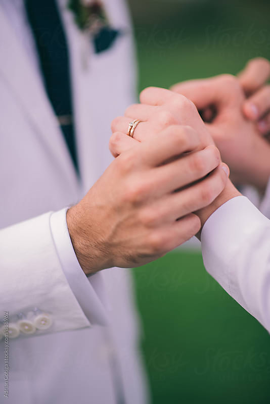 Bride and Groom holding hands showing their wedding rings by Adrian Cotiga for Stocksy United