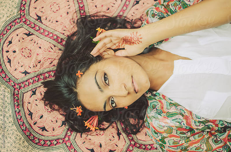 Beautiful indian woman laying on patterned blanket by Dominique Chapman for Stocksy United