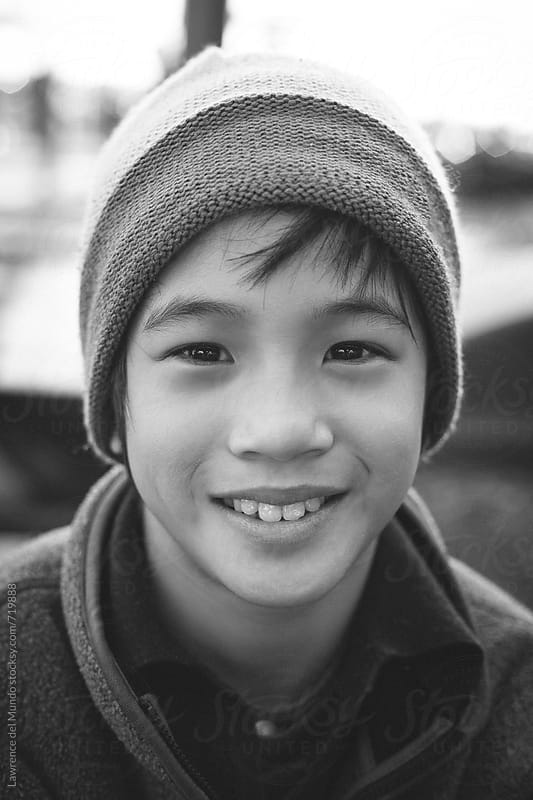 Portrait of young, smiling boy looking at the camera and wearing winter clothes by Lawrence del Mundo for Stocksy United