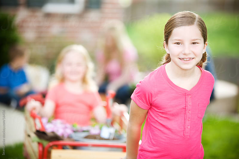 Planting: Girl Pulling Sister in Wagon by Sean Locke for Stocksy United