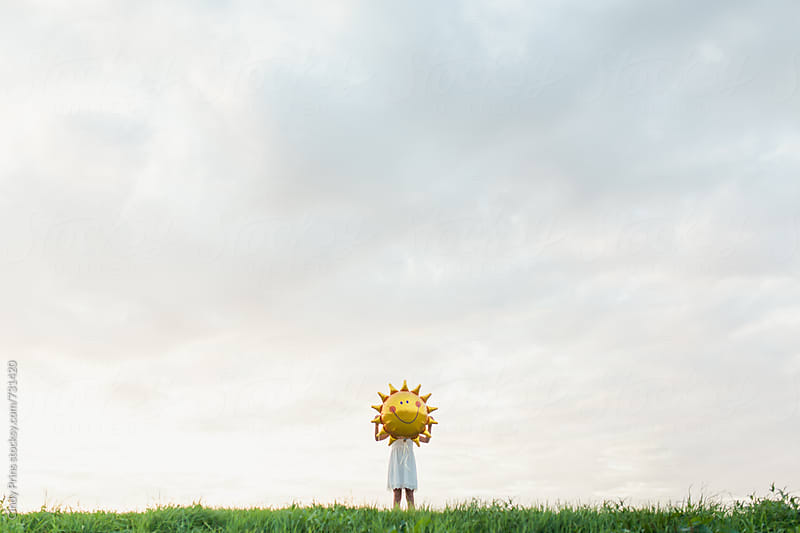 Little girl with a big sun balloon in front of her face against a cloudy sky by Cindy Prins for Stocksy United