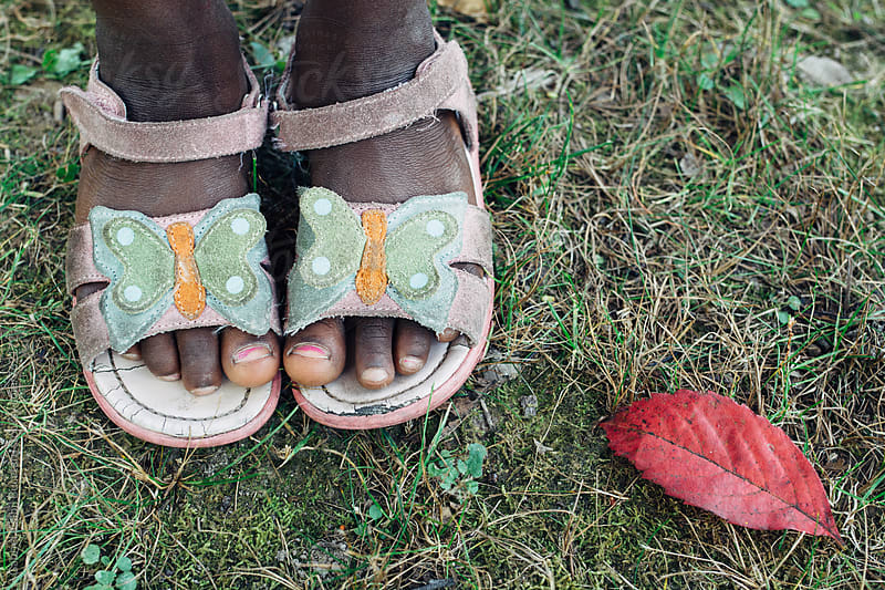 Fallen red leaf next to a black girl's feet wearing sandals by Gabriel (Gabi) Bucataru for Stocksy United