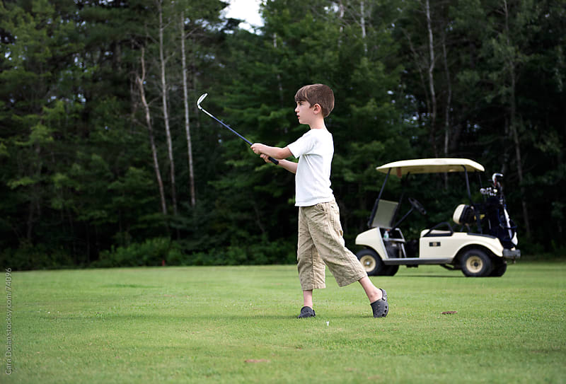 Boy playing golf finishes his swing with cart in background by Cara Dolan for Stocksy United