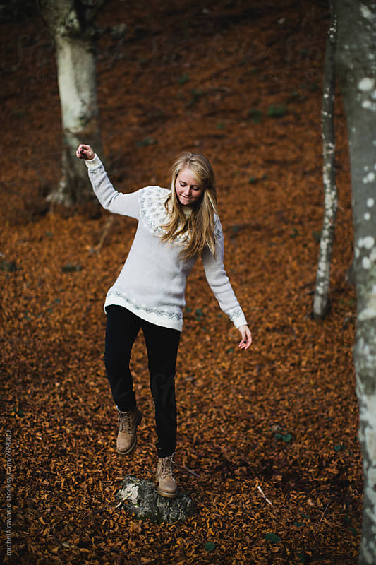 Girl balancing on a rock in the woods by michela ravasio for Stocksy United
