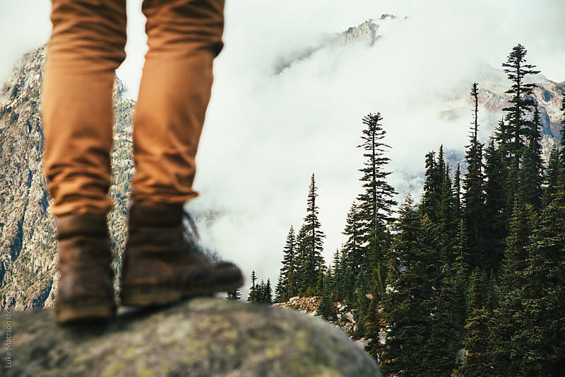 Man In Brown Leather Boots Standing On Rock Looking Upon Foggy Mountains by Luke Mattson for Stocksy United
