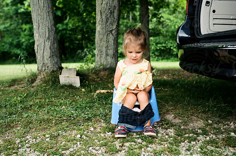 little girl takes potty break by Maria Manco for Stocksy United