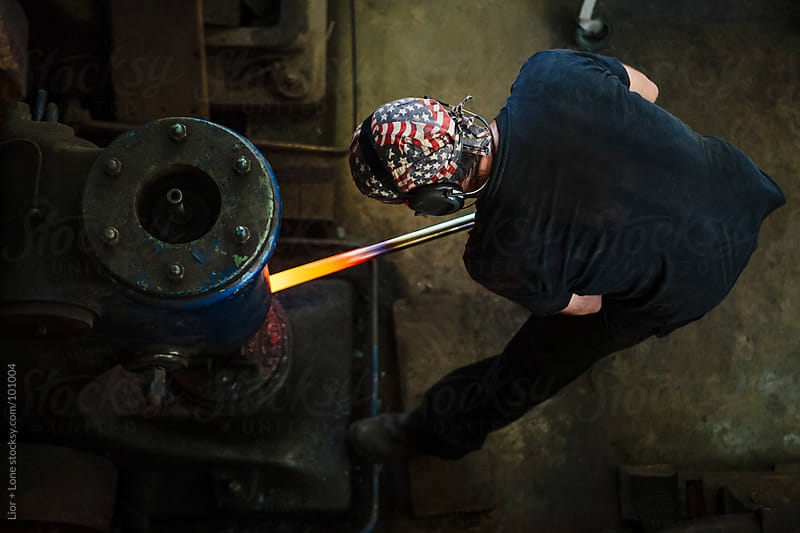 Man holding hot steel under mechanical hammer by Lior + Lone for Stocksy United
