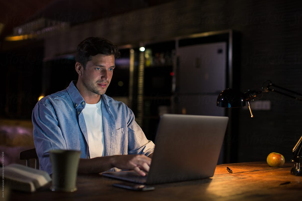 Man working from home - night time by Jovo Jovanovic - Stocksy United