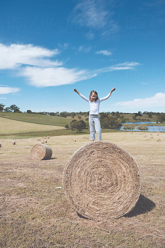country kid on hay bale by Gillian Vann for Stocksy United
