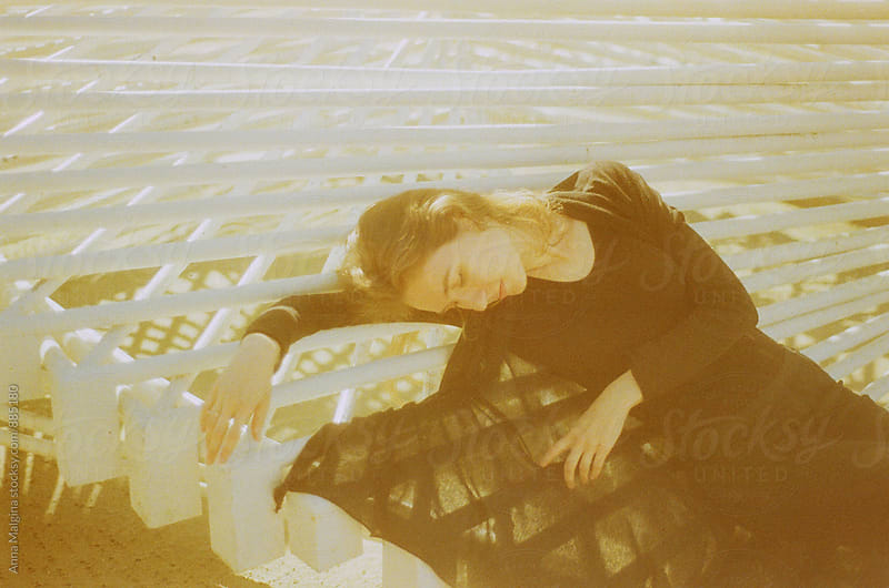 A film photo of a young beautiful woman lying on the constuction made with expired film by Anna Malgina for Stocksy United