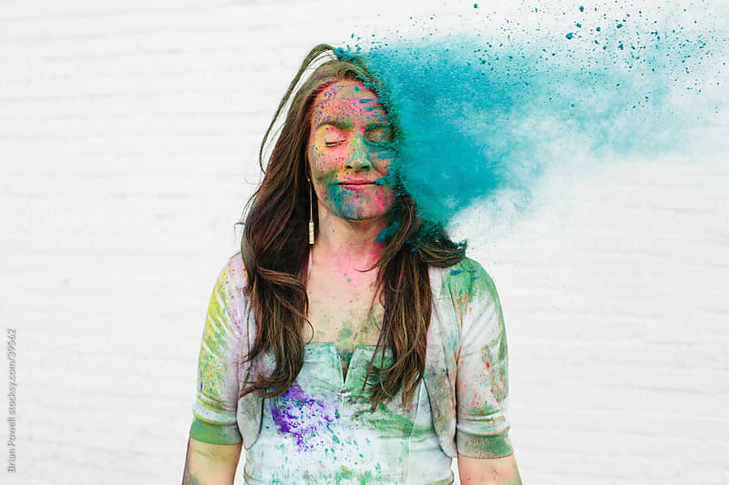 woman being hit by Holi color by Brian Powell for Stocksy United