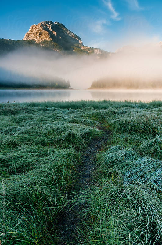 Beautiful mountain scenery with peaks above the lake in the early morning  by Dimitrije Tanaskovic for Stocksy United
