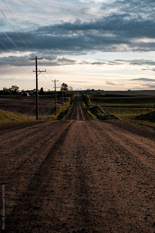 Rural dirt road leading to horizon by Riley J.B. for Stocksy United