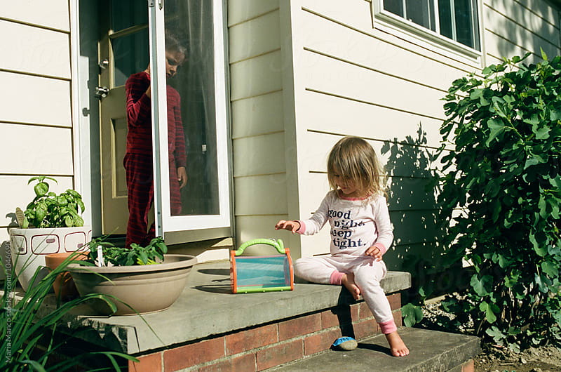 little girl sitting outside with bug house by Maria Manco for Stocksy United
