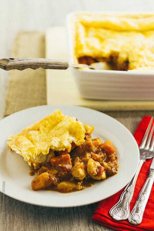 Chicken pie on plate with red napkin and cutlery by Kirsty Begg for Stocksy United
