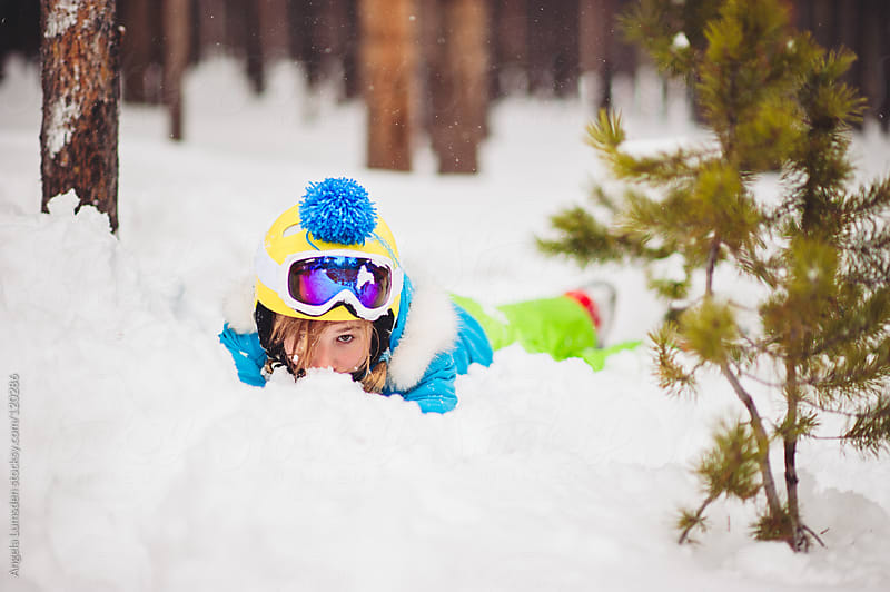 Girl in ski clothes and helmet lying in the snow by Angela Lumsden for Stocksy United