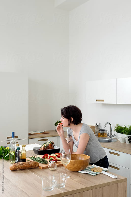 Woman eating something at kitchen while cooking by Danil Nevsky for Stocksy United