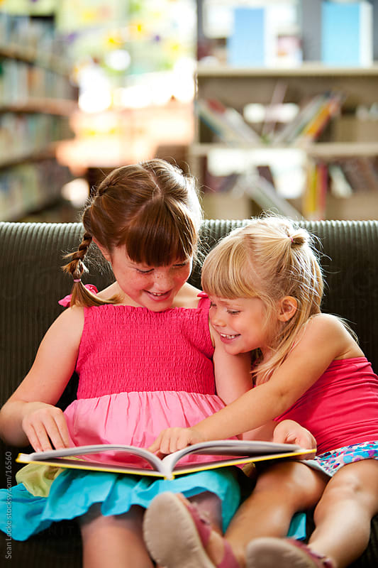 Library: Two Kids on Couch Reading by Sean Locke for Stocksy United