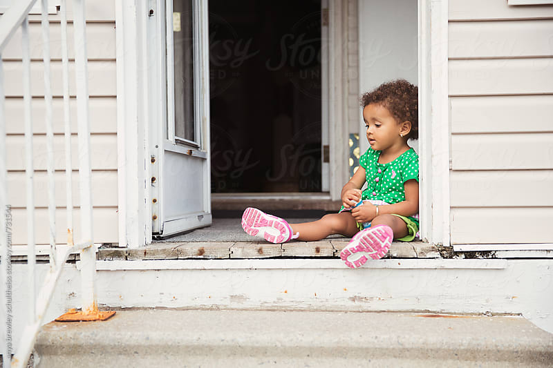 Toddler sitting happily with bubble blower at the entrance of an old wooden house by anya brewley schultheiss for Stocksy United