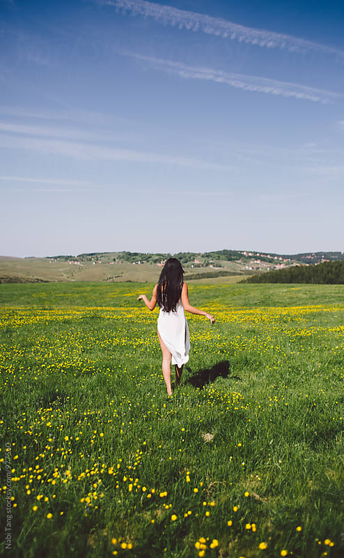 Long hair woman walking on the green grass hill in summer by Nabi Tang for Stocksy United