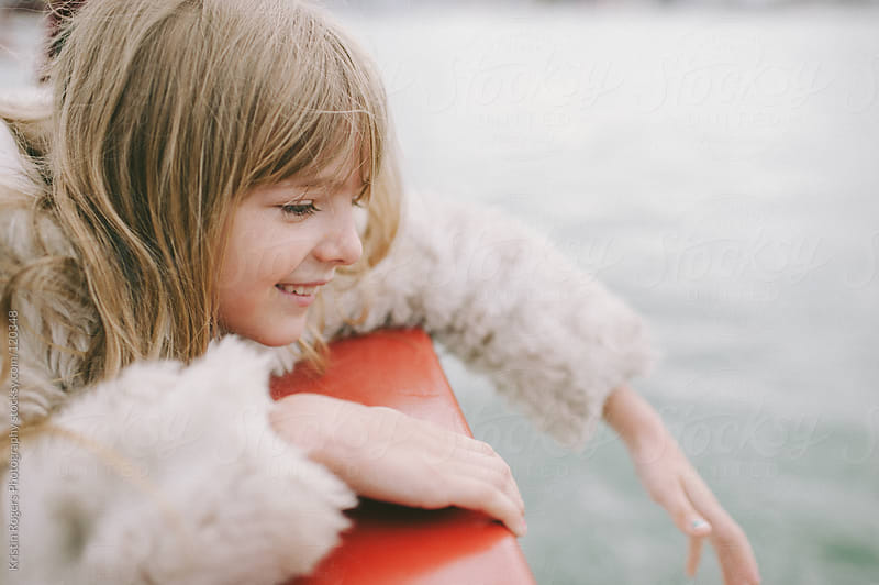 Young girl smiling as she looks over boat edge by Kristin Rogers Photography for Stocksy United