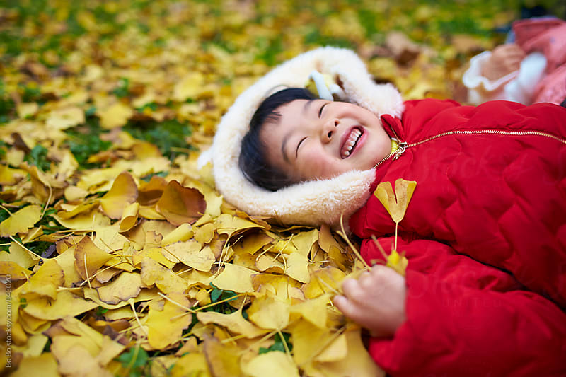 little asian girl lying on the ground with leaf around by Bo Bo for Stocksy United