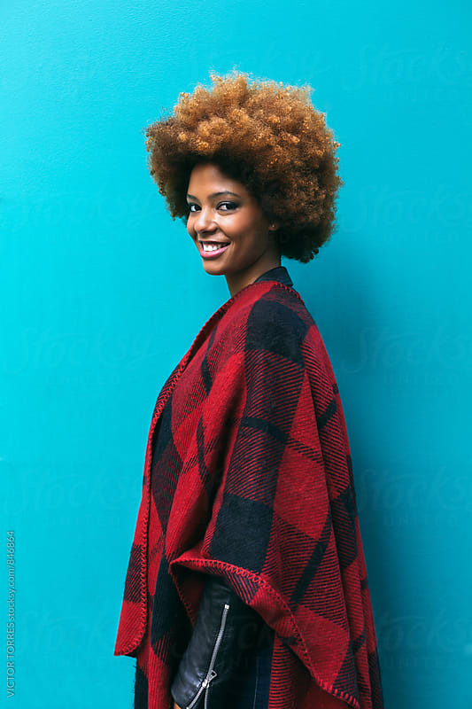 Beautiful Afro Woman over a Blue Background by VICTOR TORRES for Stocksy United