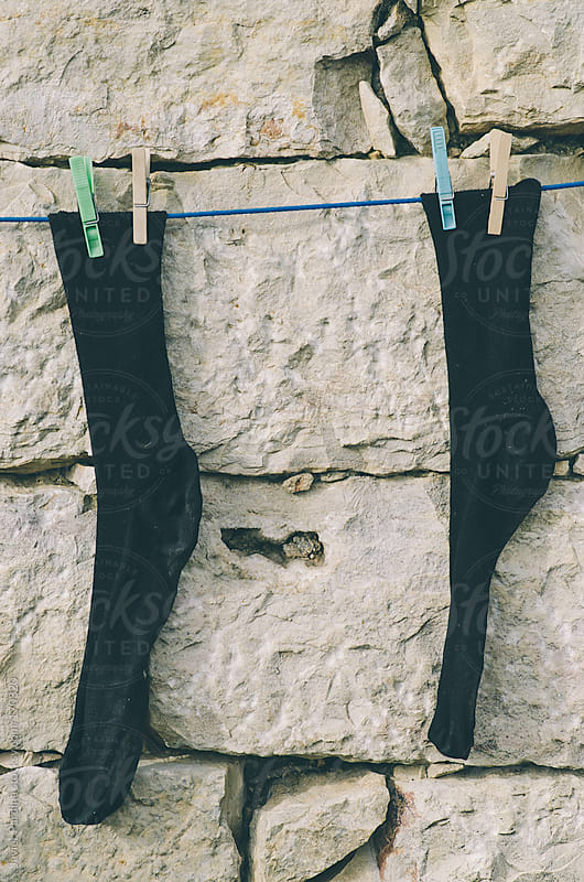 socks hung on a wall to dry by Javier Pardina for Stocksy United