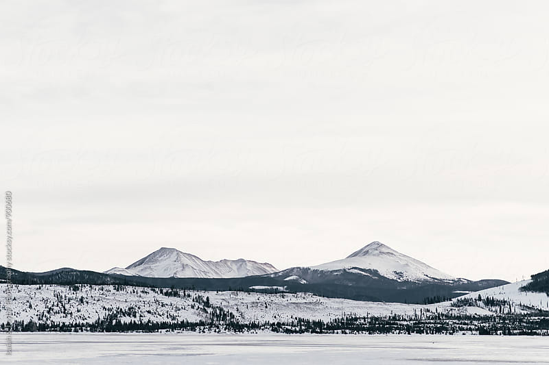 Frozen lake & snowy topped mountain landscape by Isaiah & Taylor Photography for Stocksy United