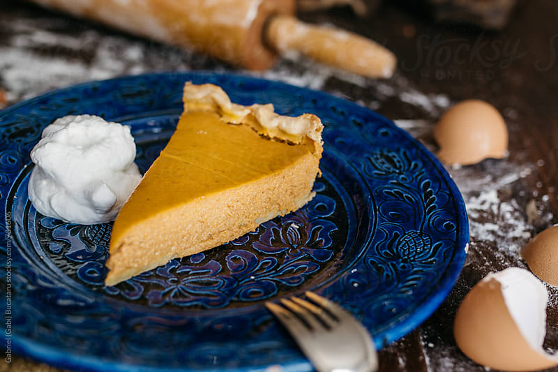 Pumpkin pie slice in a blue plate by Gabriel (Gabi) Bucataru for Stocksy United