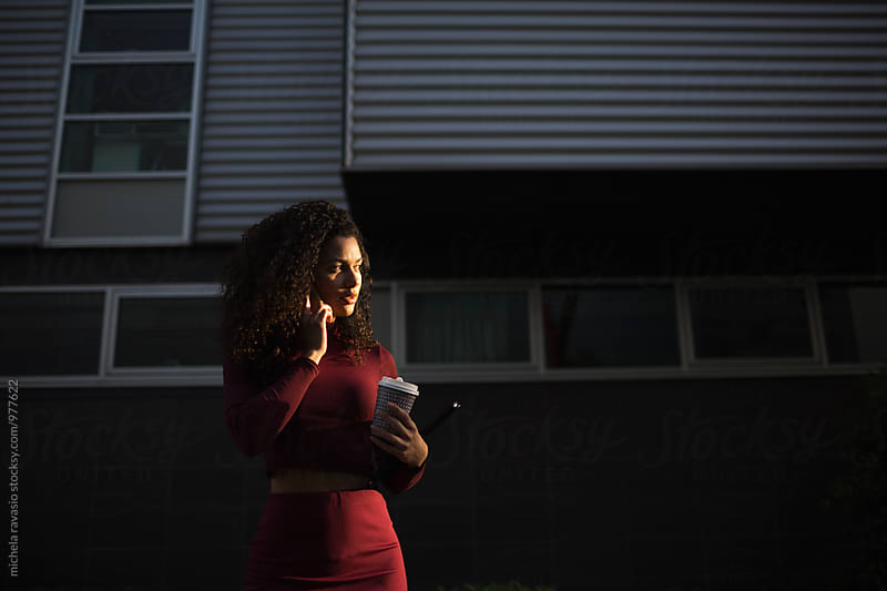 Beautiful woman, illuminated by the sun, talking on cell phone by michela ravasio for Stocksy United