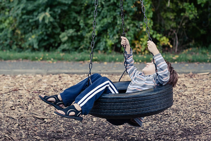 Young boy on tire swing by Kerry Murphy for Stocksy United