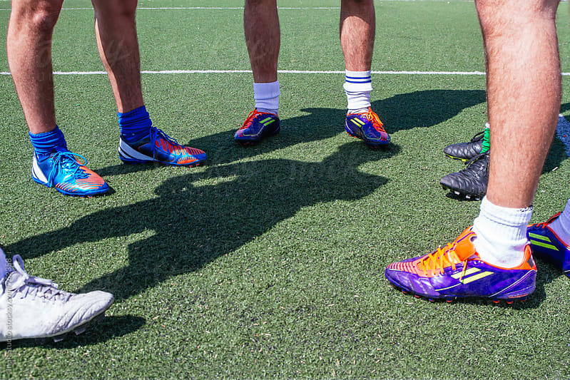 Feet of a group of soccer players on the field by Inuk Studio for Stocksy United