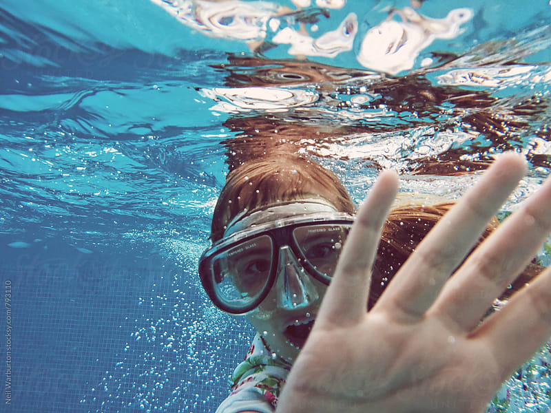 Teenage girl underwater waving at camera by Neil Warburton for Stocksy United