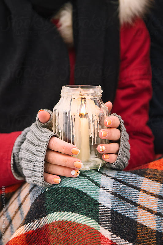 Woman's hands holding a glass can with candle by Danil Nevsky for Stocksy United