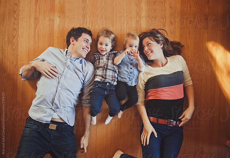 Young, happy family lying down on hardwood floors by Rob and Julia Campbell for Stocksy United