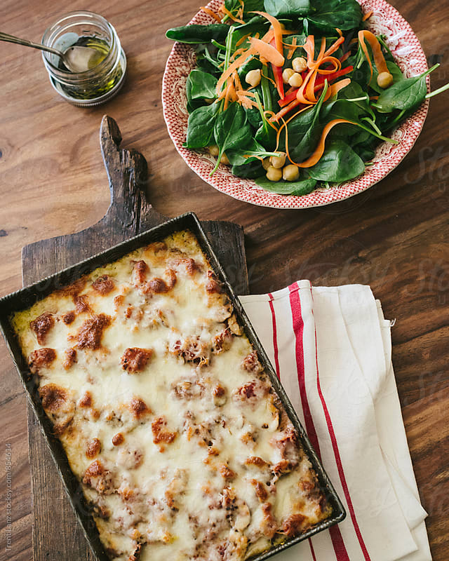 Homemade polenta bake with fresh spinach salad by Trent Lanz for Stocksy United