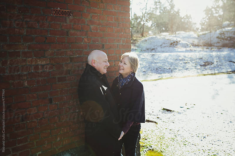 Happy older middle aged couple (fifties)  enjoying each other near brick wall outside in winter by Rob and Julia Campbell for Stocksy United