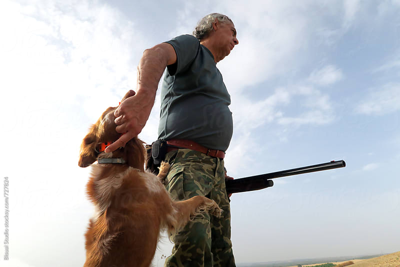 A hunter with his dog in the countryside, Granada by Bisual Studio for Stocksy United