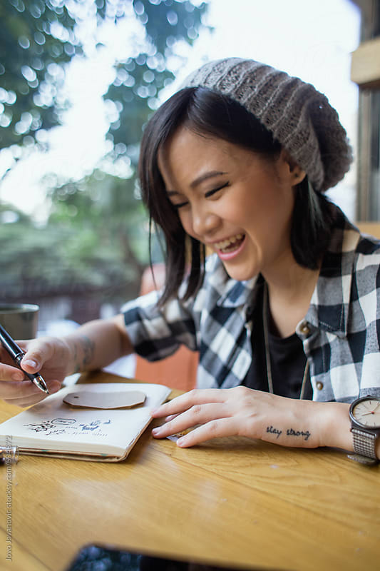Asian woman smiling and writing in her diary by Jovo Jovanovic for Stocksy United
