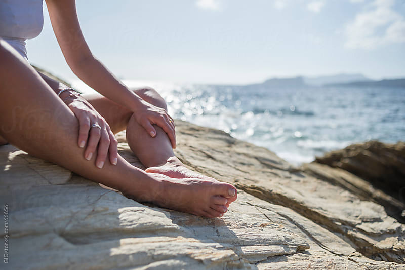 Woman relaxing on a rock in the beach by GIC for Stocksy United